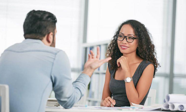 Entrevista de emprego na qual uma mulher analisa o perfil profissional do candidato