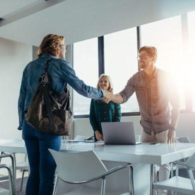 Contratação de funcionários: Duas pessoas apertando as mãos após uma entrevista de emprego