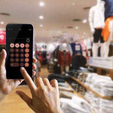 Consumidor fazendo contas em uma calculadora em uma loja