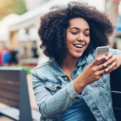 Mulher sentada mexendo em seu celular, abrindo um SMS Marketing