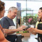 Casal de idosos pagando uma compra em uma loja que investiu em marketing para terceira idade
