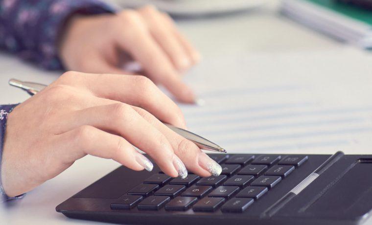 Pessoa calculando a margem de lucro ideal do negócio dela em um computador