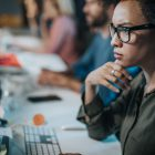 Mulher visualizando dados sensíveis de seus clientes em um computador